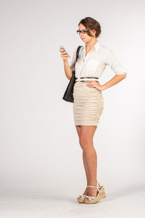 secretary skirt: Secretary girl in a short beige skirt with sunglasses, bag and mobile phone Stock Photo