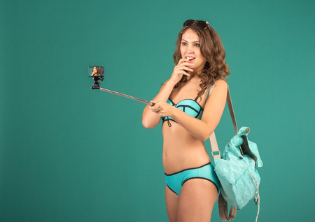 open girl: Hipster girl making selfie with action camera on green background wearing swimwear.