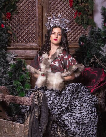 stage make up: Pretty woman in carnival dress with stage make up sitting in a beautiful sleigh on christmas tree background.