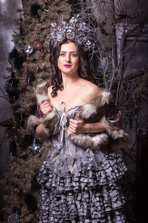 stage make up: Pretty woman in carnival dress with stage make up on christmas tree background. Stock Photo