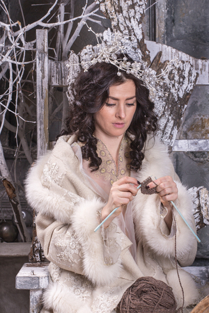 knitting needles: Brunette  woman in Russian traditional dress with knitting needles in her hands
