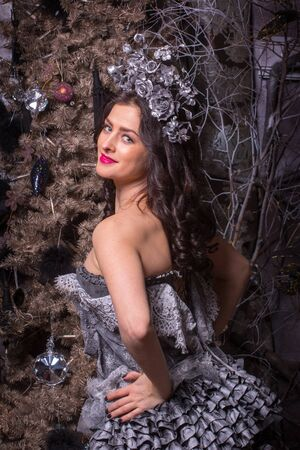 stage make up: Pretty brunette woman in historical vintage russian dress with stage make up on christmas tree background.