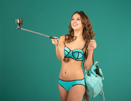 girl action: Hipster girl making selfie with action camera on green background wearing swimwear.