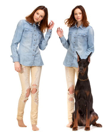 blue background: Beauty red Twins in jeans shirt with big black doberman dog, isolated on white
