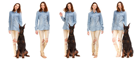 blue and white: Beauty red girl in jeans shirt with big black doberman dog, isolated on white