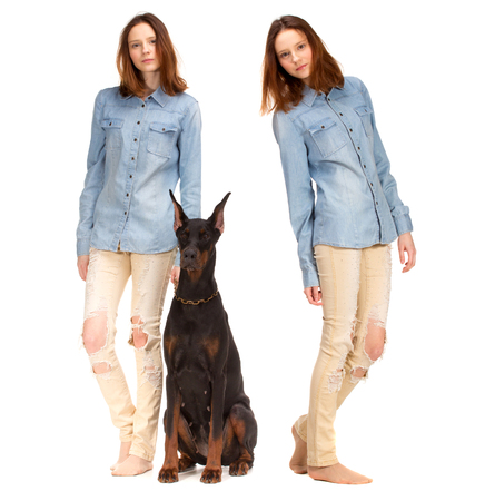 red and blue: Beauty red Twins in jeans shirt with big black doberman dog, isolated on white