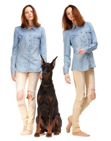 modelos hombres: Chica rojo de la belleza en la camisa de los pantalones vaqueros con el perro grande doberman negro, aislado en blanco Foto de archivo