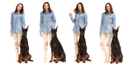 male and female: Beauty red girl in jeans shirt with big black doberman dog, isolated on white