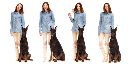 poses de modelos: Chica rojo de la belleza en la camisa de los pantalones vaqueros con el perro grande doberman negro, aislado en blanco Foto de archivo