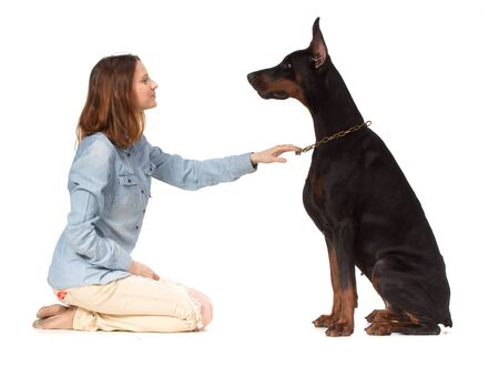 doberman: Redhead girl sitting on her knees in front of a large black doberman  dog, isolated on white