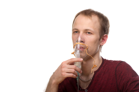 respire: Young man using nebulizer mask for respiratory inhaler Asthma Treatment isolated on a white background. Close up view.