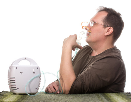 Adult man using nebulizer mask for respiratory inhaler Asthma Treatment isolated on a white background. Close up view.