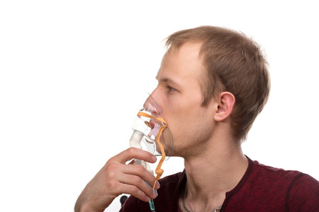 Young man using nebulizer mask for respiratory inhaler Asthma Treatment isolated on a white background. Close up view.