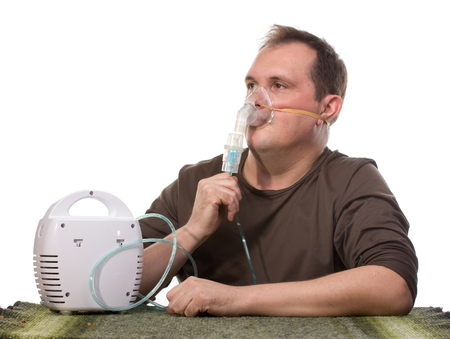 respire: Adult man using nebulizer mask for respiratory inhaler Asthma Treatment isolated on a white background. Close up view.