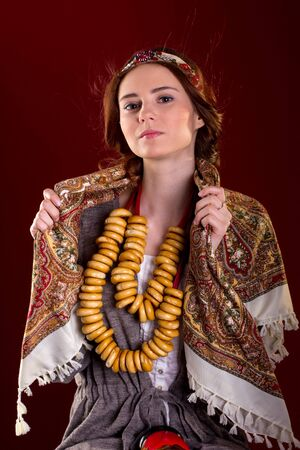 baranka: Portrait of young woman in Rissian dress, national scarf on red backgeround