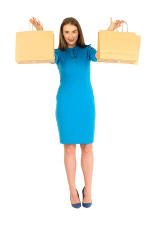 Pretty woman in blue dress posing with set of  eco frendly paper bags.