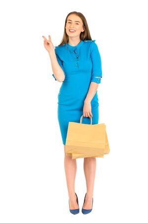 frendly: Pretty woman in blue dress posing with eco frendly paper bags. Shows ok sign. Stock Photo