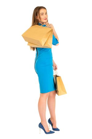 frendly: Pretty woman in blue dress posing with set of  eco frendly paper bags.