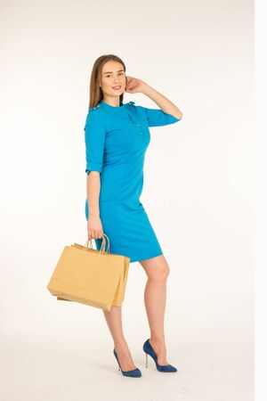 Pretty woman in blue dress posing with eco frendly paper bags
