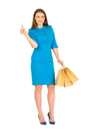 Pretty woman in blue dress posing with eco frendly paper bags. Shows ok sign. Stock Photo