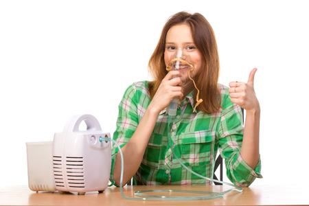 Young girl using nebulizer mask for respiratory inhaler Asthma Treatment isolated on a white background. Close up view.