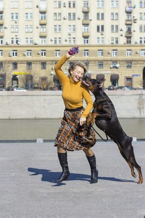 persona saltando: juego activo. Mujer jugando con perro grande dobermann femenina