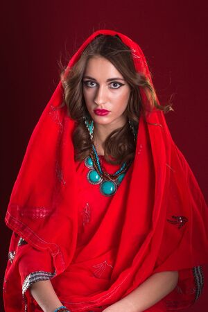sari: Pretty caucasian woman wearing in red indian sari and scarf on her head, close up portrait