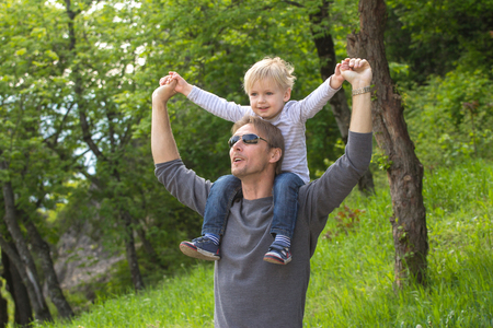 Blond boy sitting on fathers shoulder outdoors