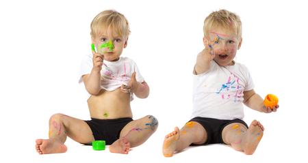 hermanos jugando: Hermanos de gemelos que juegan con la pintura, aislados en blanco.