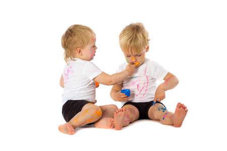 brothers playing: Hermanos de gemelos que juegan con la pintura, aislados en blanco.