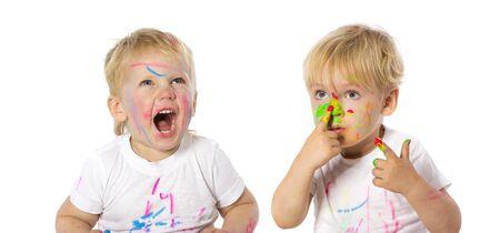 Hermanos de gemelos que juegan con la pintura, aislados en blanco.