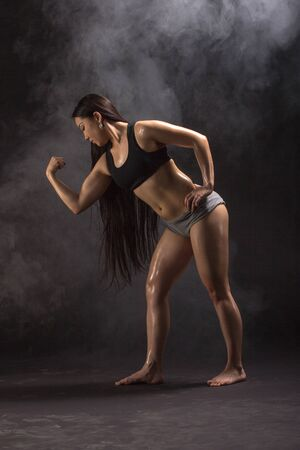 asian abs: Strong and beautiful. Studio shot of a gorgeous sporty woman looking to hand showing her biceps on black background