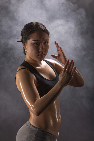 asian abs: Strong and beautiful. Studio shot of a gorgeous sporty boxer woman on black background