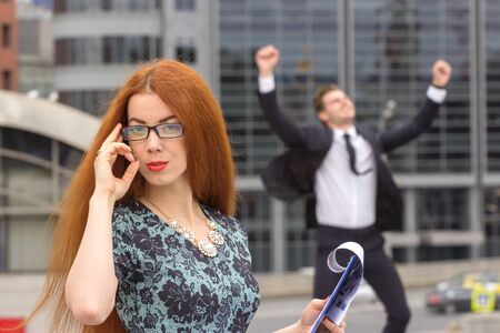 jumping businessman: Red-haired woman posing on jumping businessman background Stock Photo