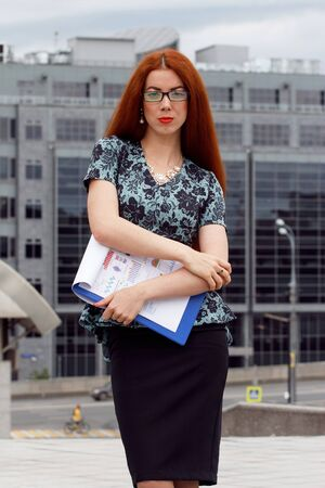 lawer: Young smiling businesswoman with heap of papers