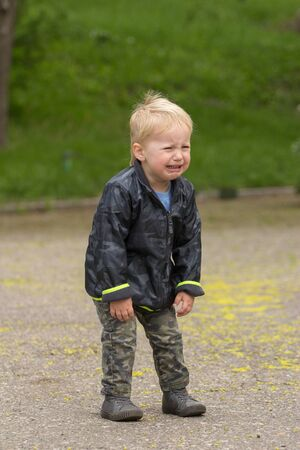 fussy: Blond kid crying very loud on the street Stock Photo