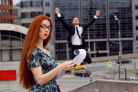 jumping businessman: Ginger woman posing on jumping businessman background
