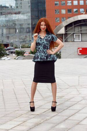lawer: Ginger smiling business woman posing on urban background