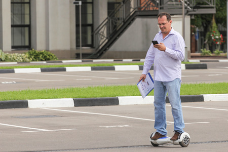 electronic balance: Business man riding an electronic scooter outdoors - personal portable eco transport, hover board, gyro scooter, hyroscooter, smart balance wheel