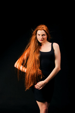 long red hair: Beauty ginger Girl Portrait. Healthy Long Red Hair. Beautiful Young Woman on black