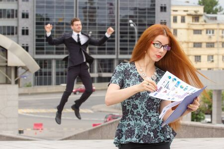 jumping businessman: Red-haired woman with abstract grafics, posing on jumping businessman background