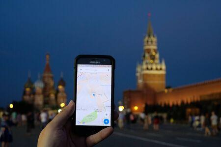 Moskou, Rusland - 31 juli: Mannenhand met een Samsung Galaxy-smartphone met een lopende Google Maps-applicatie op de achtergrond van de muur van het Kremlin en de Sint Basiliuskathedraal