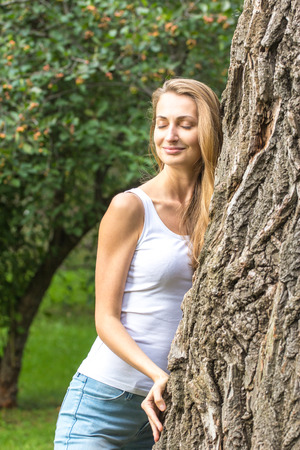 environmentalist: Close up Thoughtful Young Nature-Lover Woman Hugging a Huge Tree Trunk at the Park with Happy Facial Expression. Stock Photo