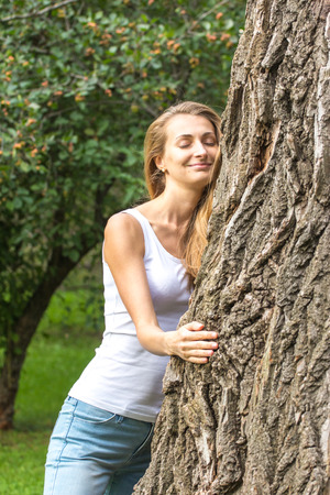 huge tree: Close up Thoughtful Young Nature-Lover Woman Hugging a Huge Tree Trunk at the Park with Happy Facial Expression. Stock Photo