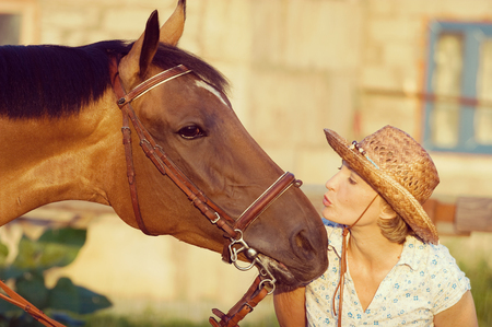 Woman in hat kissing brown horse. Vintage filtered image. Stock Photo