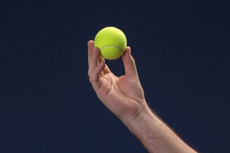 Hand hold Tennis ball on blue background