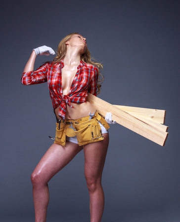 Portrait of young female construction carpenter worker carrying wooden boards on arm