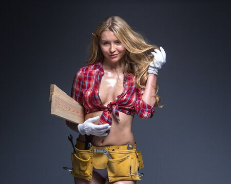 oiled: Portrait of young female construction carpenter worker carrying wooden boards on arm