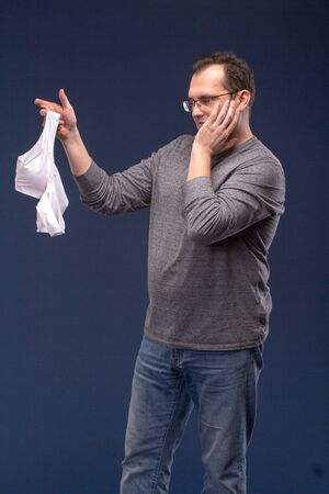adultery: Shocked Man holding a womans bra on blue background.
