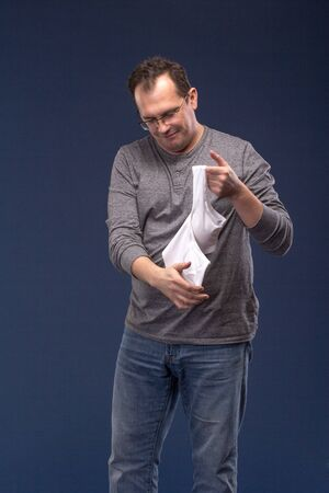 unfaithfulness: Shocked Man holding a womans bra on blue background.